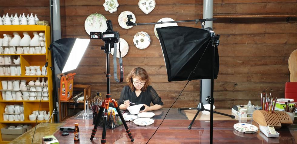 그림공예 강사님이 강의하시는 모습입니다, 책상위에 다양한 접시가 놓여 있고 하나의 접시를 선택하여 그림을 그리고 있는 모습입니다, 강사님의 양쪽에는 영상촬영용 라이트가 강사님을 비추고있으며, 가운데는 카메라가 놓여져있습니다